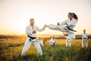 Female karate fighter trains kick in flight